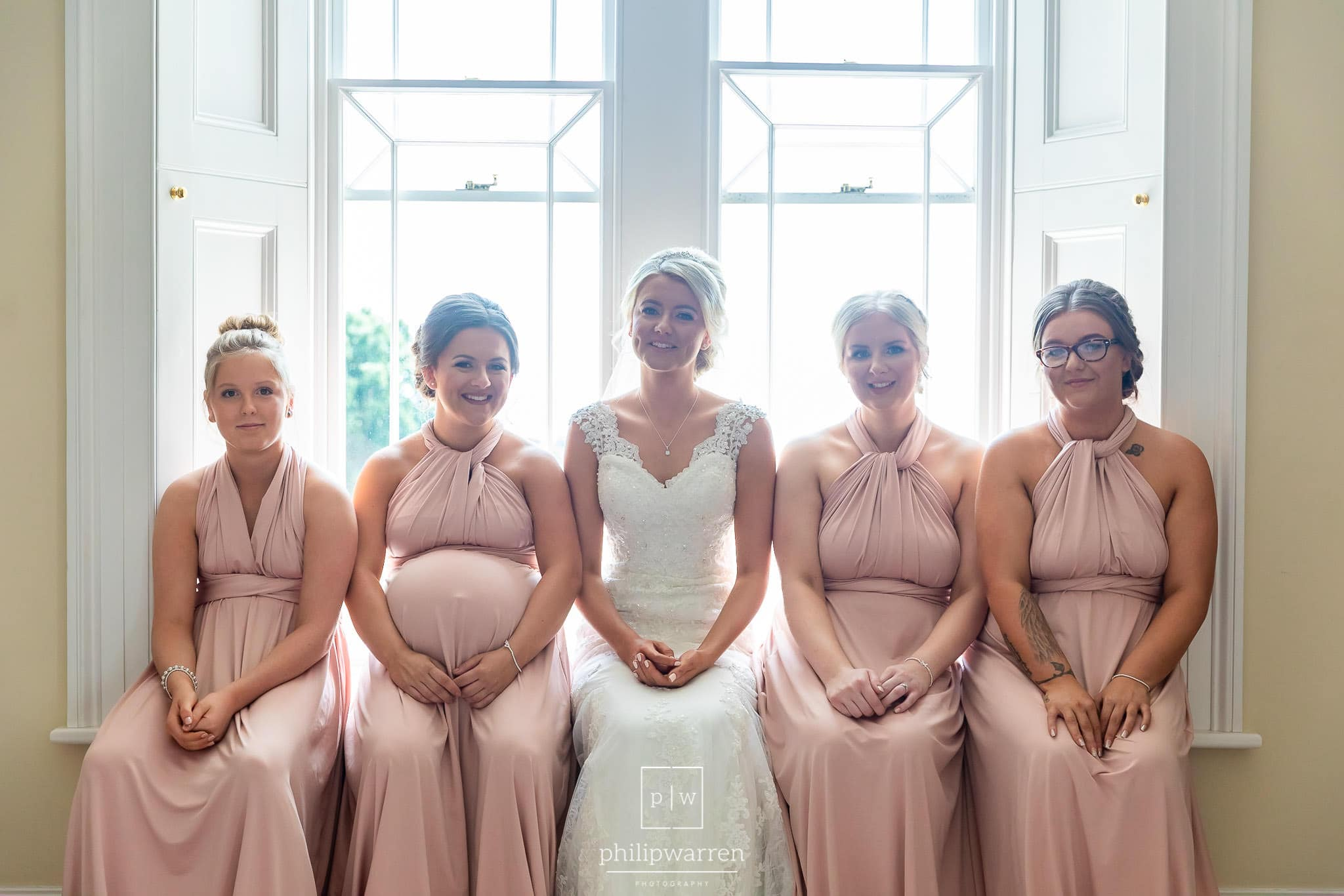 bride and her 4 bridesmaids sitting together in their pink bridesmaids dresses sitting in the window in the south wales wedding venues
