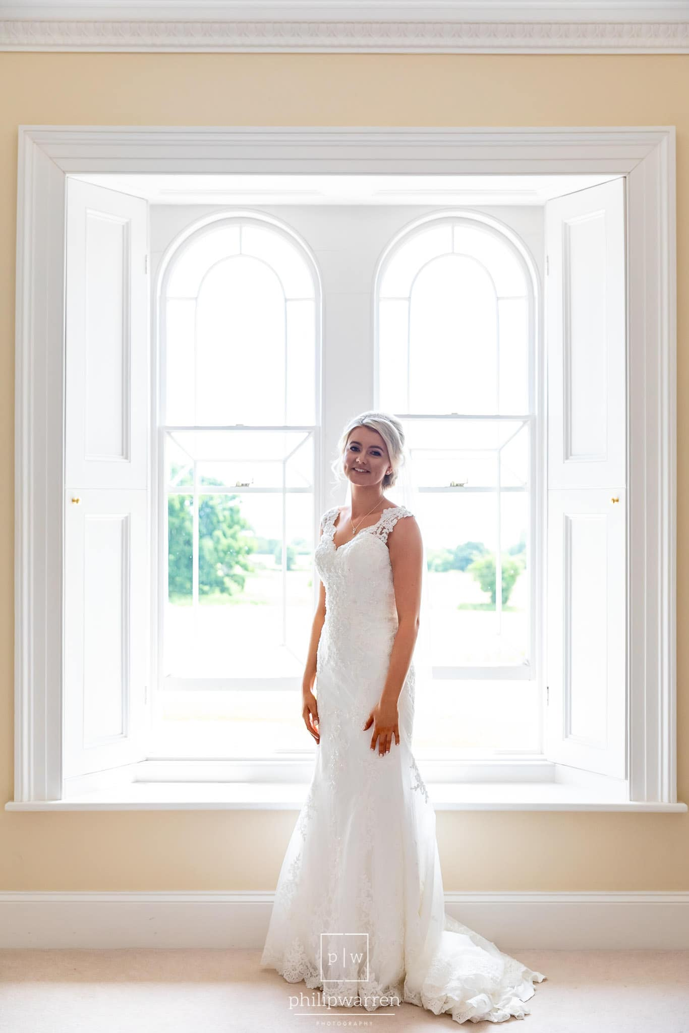 bright and light bridal protrait in the window of one of the bedrooms just before the wedding ceremony