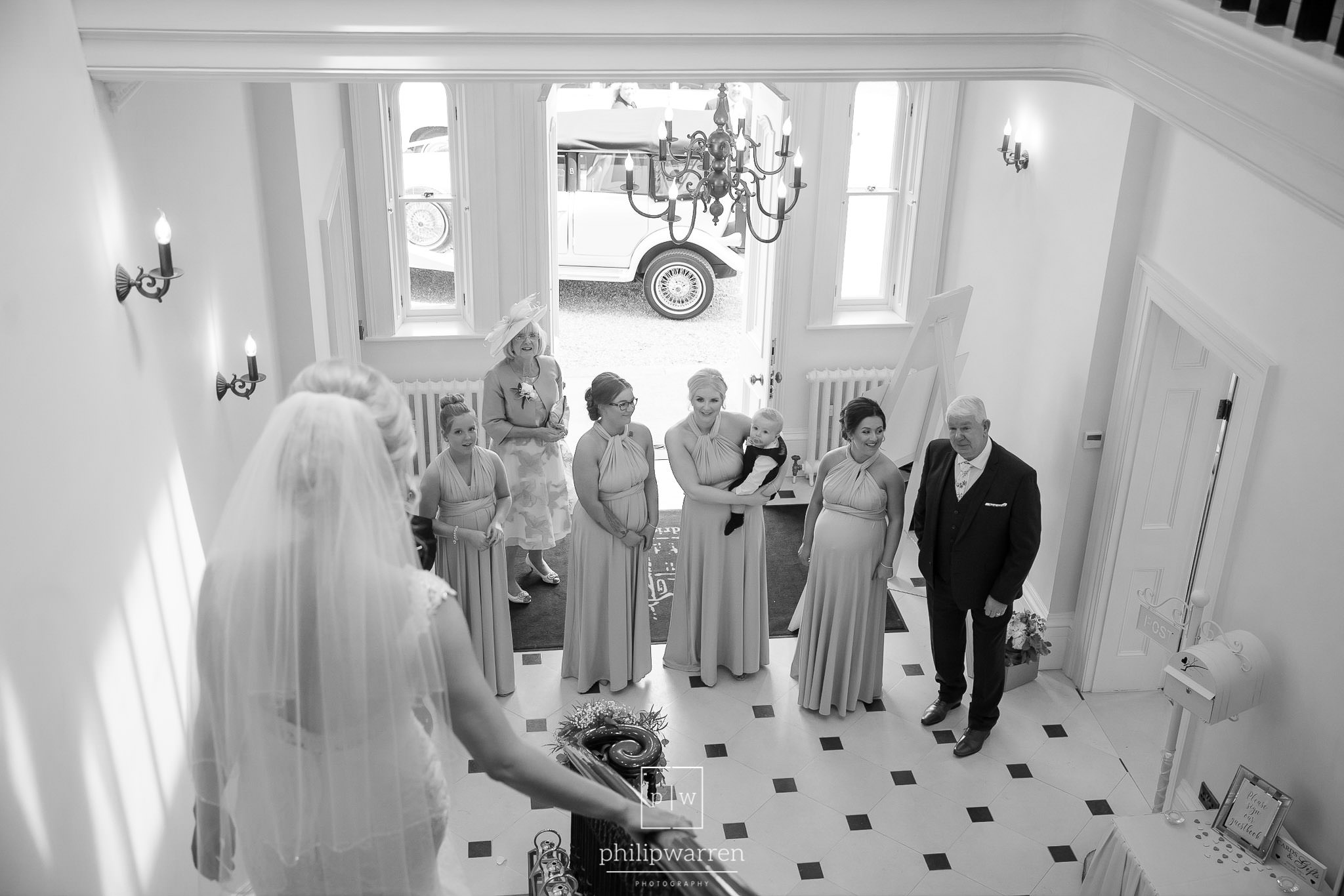 black and white photo taken from behind the bride with her mother and father and bridesmaids waitingat at he bottom of the stairs at this welsh wedding venue