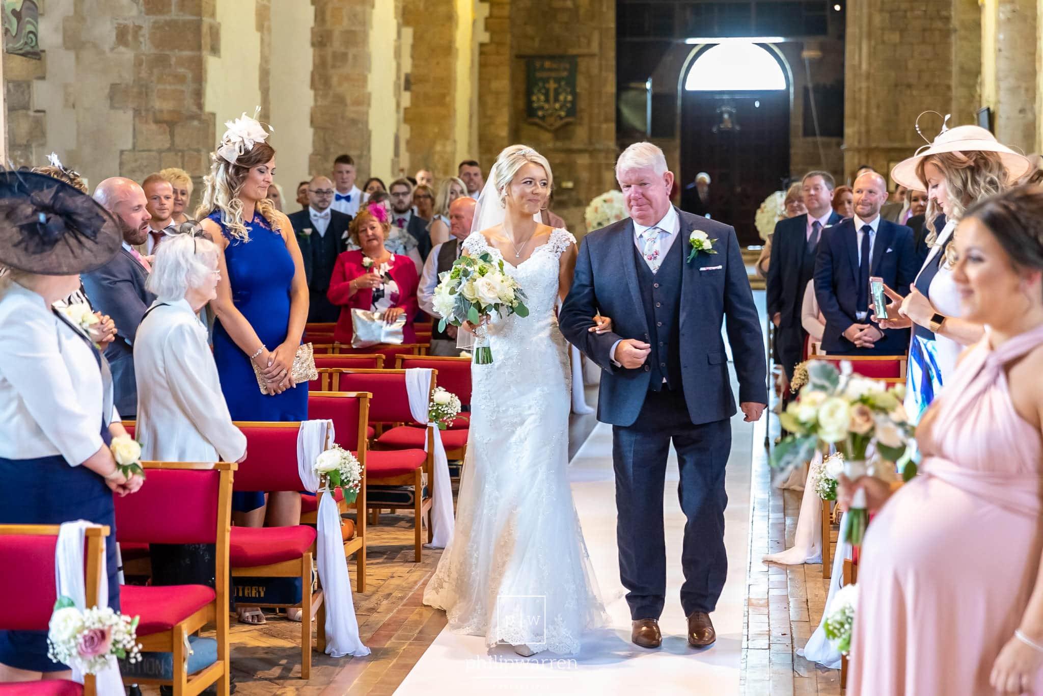 bride and her dad walking down the aisle at st marys church in chepstwo smiling with all the guests standing around them