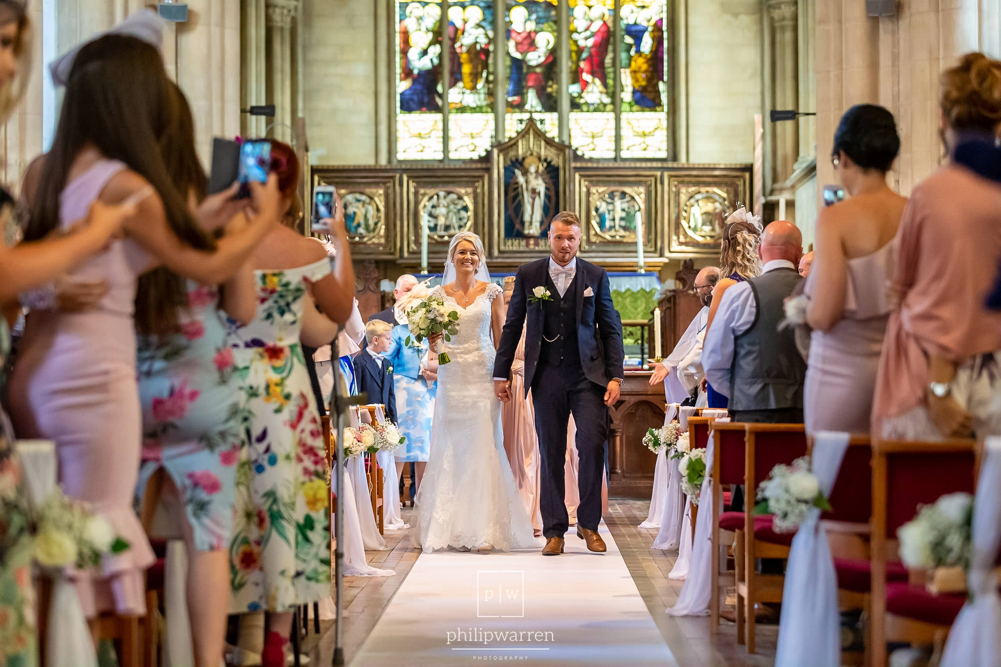 walking back down the aisle in st marys church in chepstow after getting married. The bride is carrying her bouquet and holding hands with her new husband